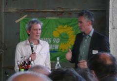 Frau mit Mikrofon und Mann bei einer Diskussion oder Vortrag, im Hintergrund Plakat »Bündnis 90 Die Grünen«.