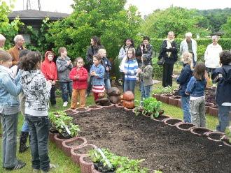 Kleingärtner im Gelände feiern die Eröffnung des »Schulkleingartens«