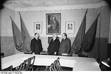 Raum mit Fahnenschmuck und Thälmannbild, davor: Walter Ulbricht, Wilhelm Pieck und Otto Grotewohl.