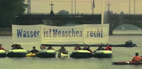 Protestaktion: Aneinander gekoppelte Boote mit Transparent: »Wasser ist Menschenrecht«.