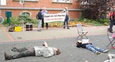 Aktion 2007 gegen CO-Pipeline. Darstellung eines Gasunfalls. Menschen liegen auf dem Boden. Transparent der Linken Liste Düsseldorf »Stoppt die CO-Pipeline«.