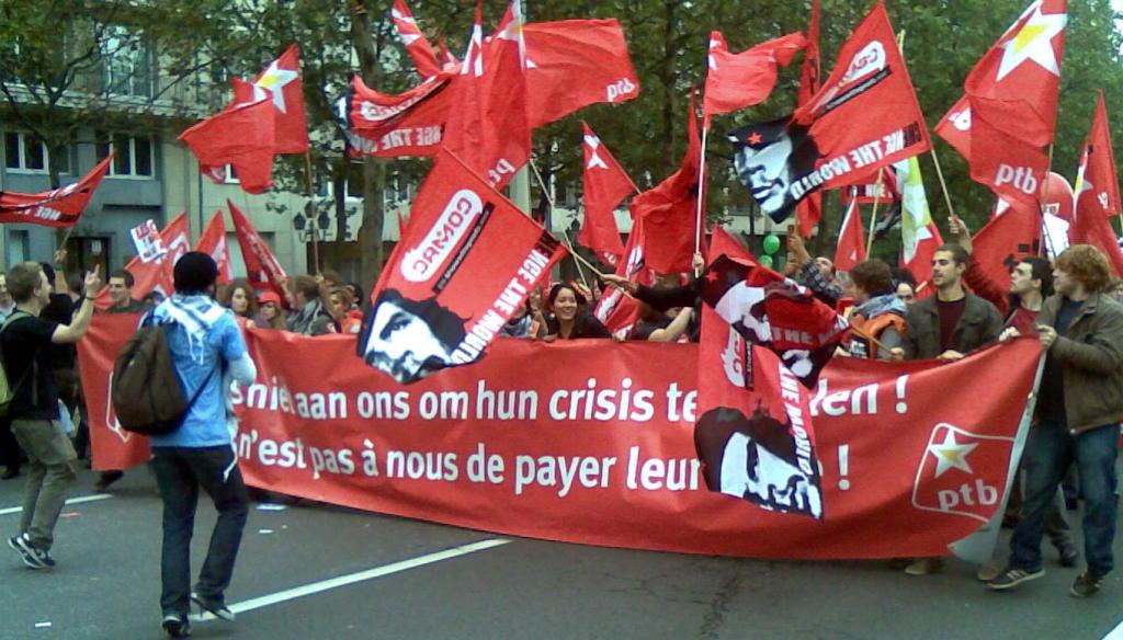 Demonstranten mit Transparenten und roten Fahnen.
