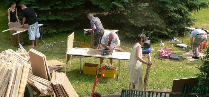 Sechs Menschen in einem Garten bauen Stelltafeln.