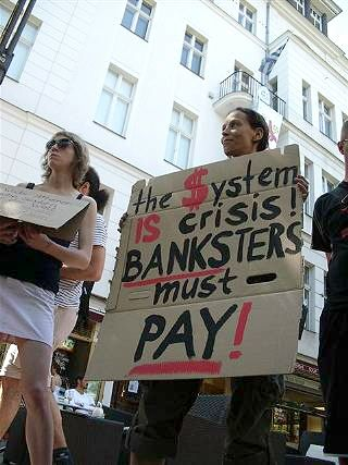 Demonstrantin mit Plakat: »the $ystem is crisis! Banksters must pay!«.